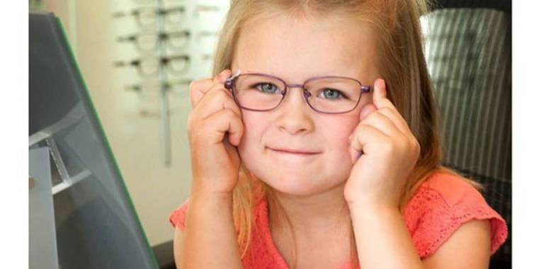 kindergarten child trying on eyeglasses