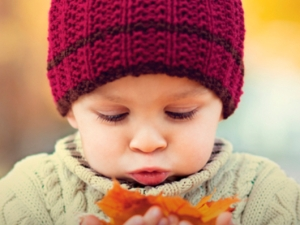 young child looking at leaves